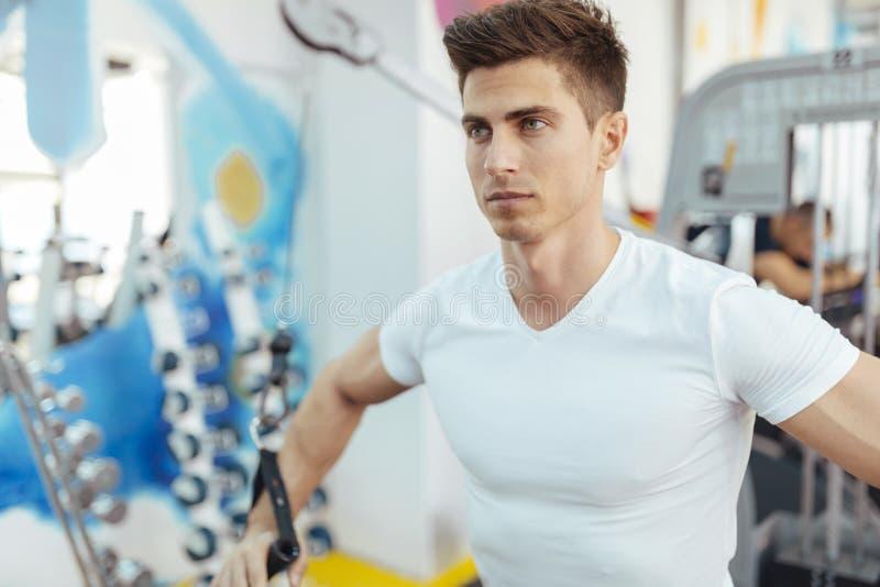 在干净的现代健身房的英俊的人训练 库存照片