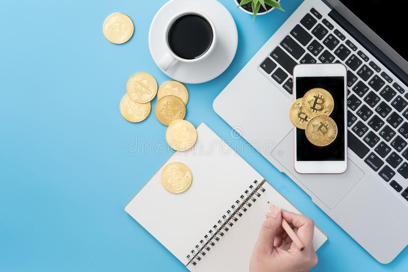 在干净的蓝色有bitcoin和咖啡杯的,工作区设计办公室运转的书桌上认为金钱概念隔绝的妇女, 免版税库存图片