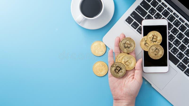 在干净的蓝色有bitcoin和咖啡杯的,工作区设计办公室运转的书桌上认为金钱概念隔绝的妇女, 免版税库存照片