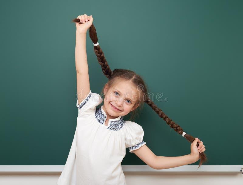 在干净的黑板,做鬼脸和情感的学校学生女孩开放胳膊,在一套黑衣服,教育概念,演播室穿戴了 库存照片