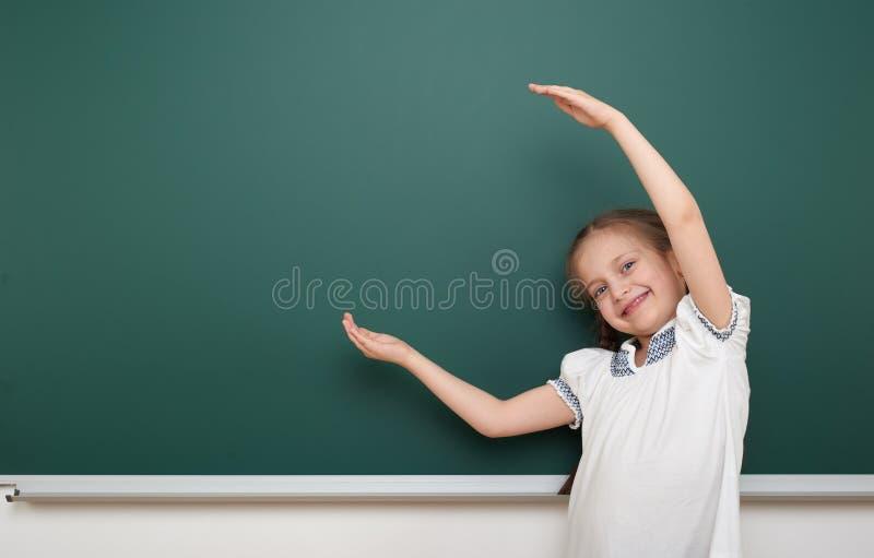 在干净的黑板,做鬼脸和情感的学校学生女孩开放胳膊,在一套黑衣服,教育概念,演播室穿戴了 库存图片