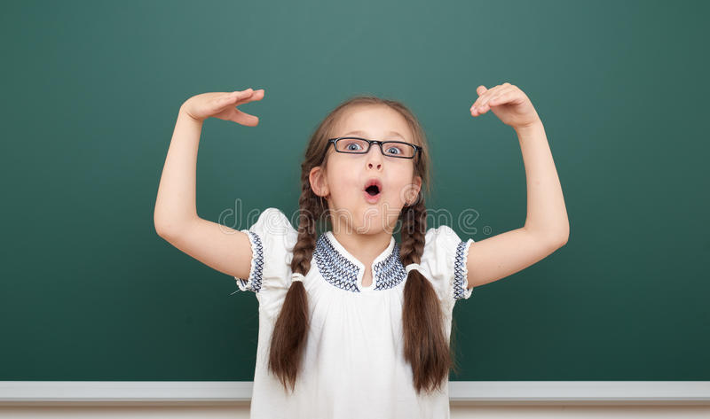 在干净的黑板,做鬼脸和情感的学校学生女孩开放胳膊,在一套黑衣服,教育概念,演播室穿戴了 免版税库存照片