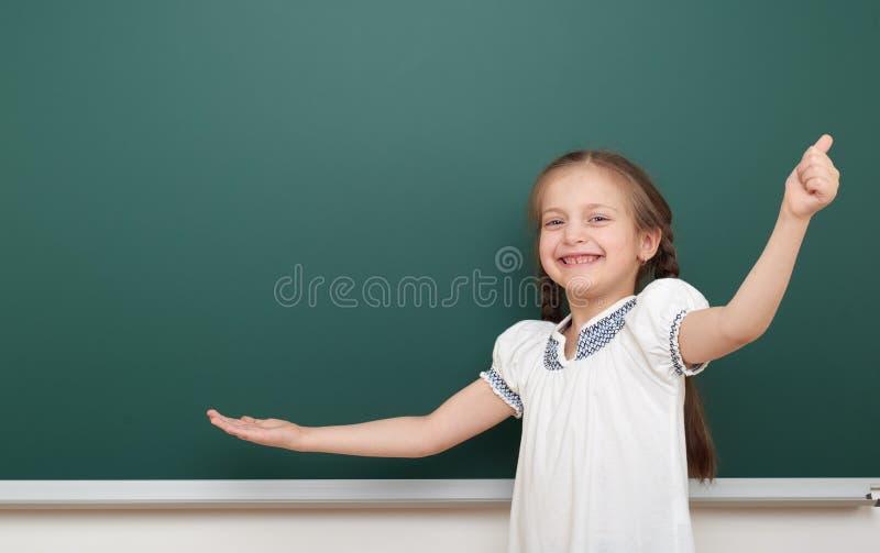 在干净的黑板,做鬼脸和情感的学校学生女孩开放胳膊,在一套黑衣服,教育概念,演播室穿戴了 免版税图库摄影
