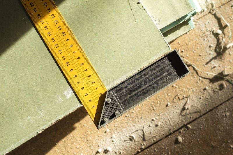 在干式墙板料的壁角统治者 堆石膏板为建筑做准备 在视图之上 免版税库存图片