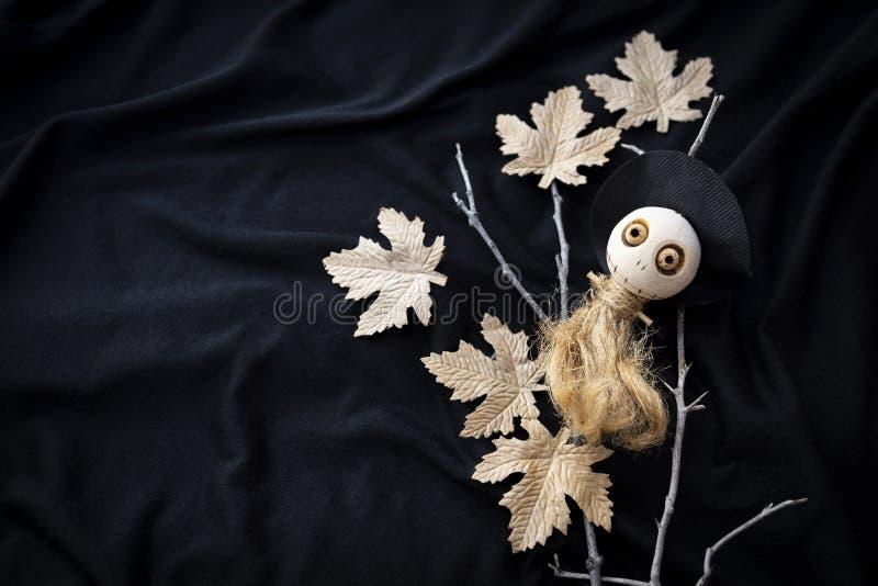 在干燥分支和纸叶子的逗人喜爱的木巫婆玩偶在被弄脏的黑织品纹理背景 免版税库存图片