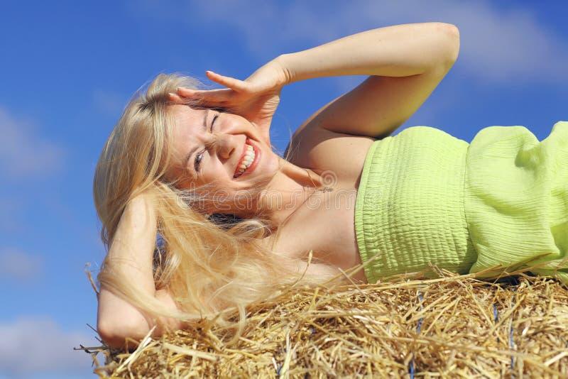 在干草的年轻白肤金发的女孩 免版税图库摄影