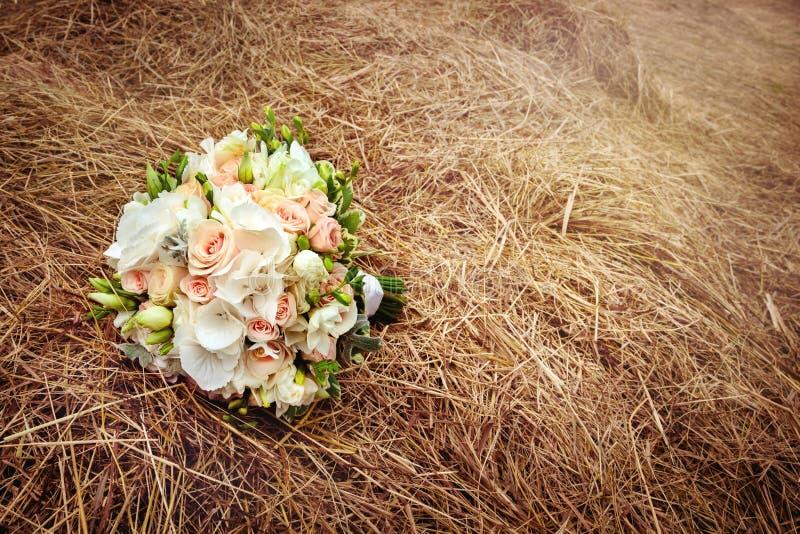 在干草领域的婚礼花 土气样式 库存图片