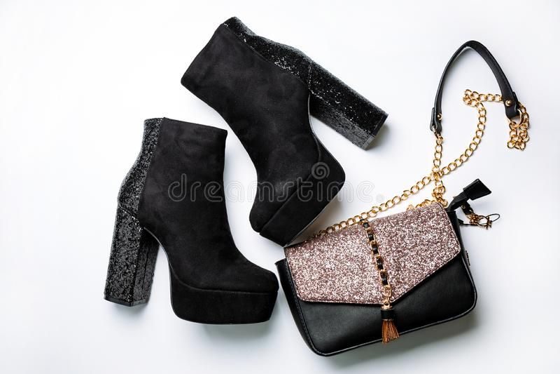 在平台和厚实的脚跟的黑绒面革脚腕起动有闪闪发光的和与闪闪发光的一个黑袋子在白色的挡水板 图库摄影
