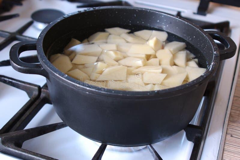 在平底深锅的土豆在气体滚刀 库存图片