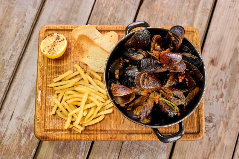 在平底深锅的贝类淡菜用柠檬和油炸物 图库摄影
