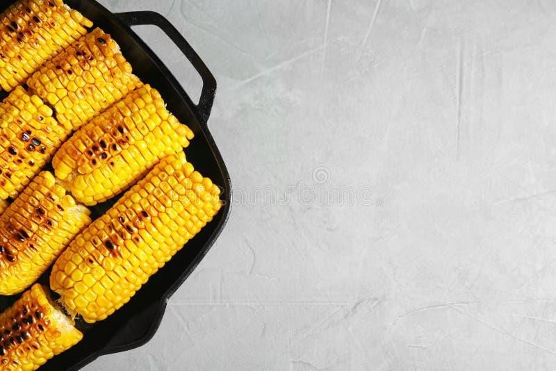 在平底锅和空间的新鲜的烤鲜美玉米棒子在轻的背景的文本的 免版税库存图片