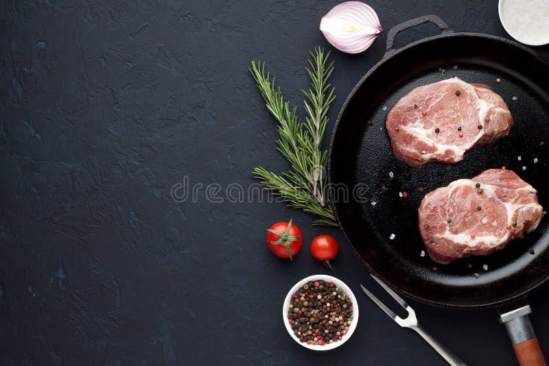 在平底锅的两块未加工的牛排用迷迭香和胡椒在黑暗的石背景 免版税库存图片