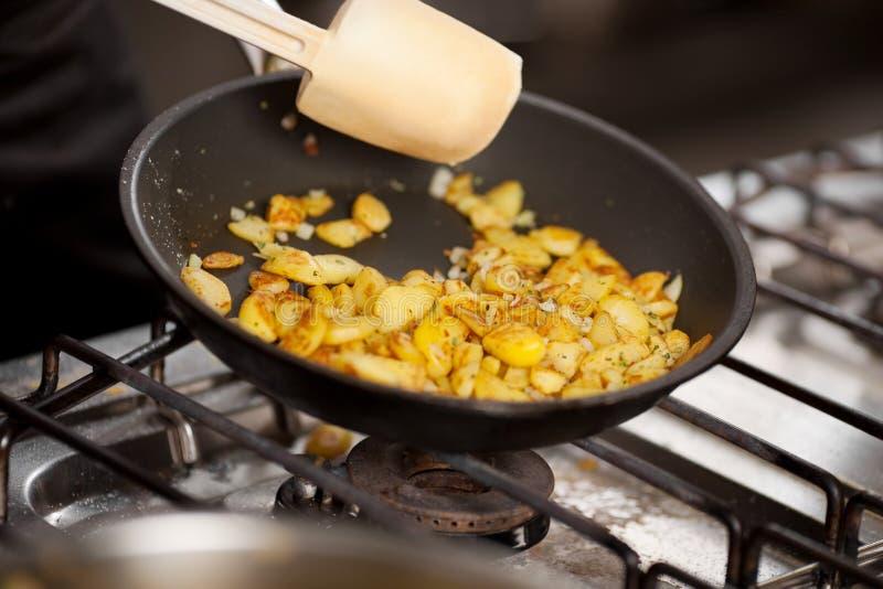 在平底锅的切的土豆在火炉 库存图片