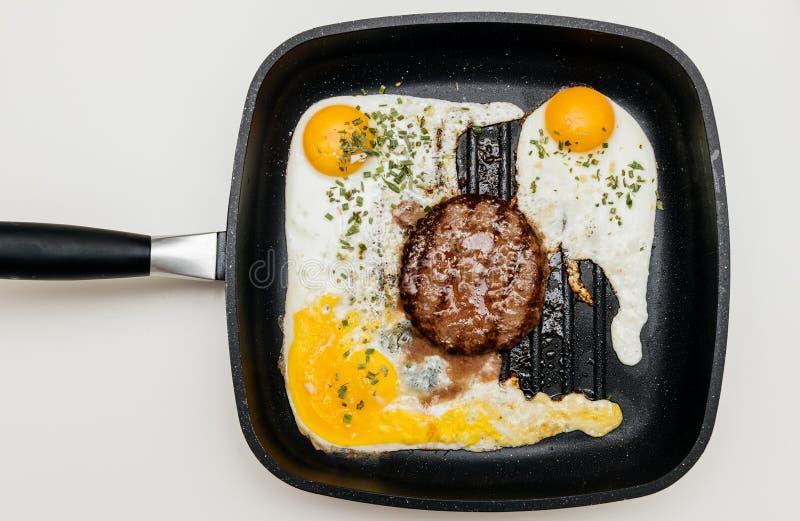 在平底锅的可口汉堡用从上面被看见的卵黄质鸡蛋 库存图片