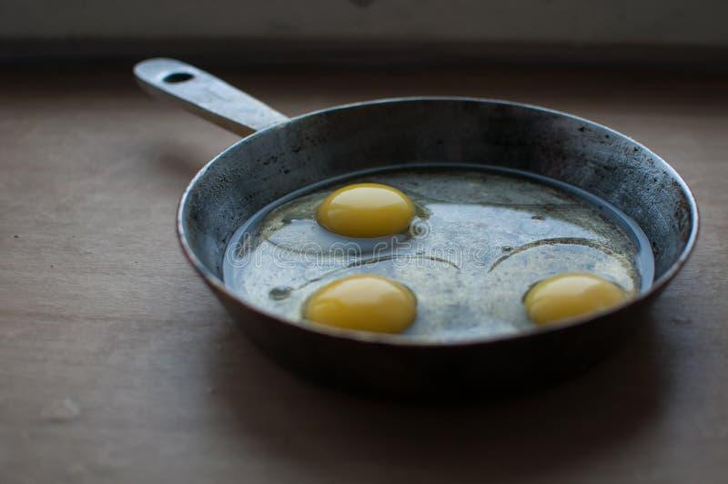 在平底锅的未加工的鸡蛋 库存照片