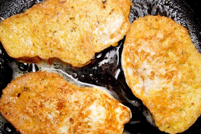 在平底锅的油煎的油煎方型小面包片 免版税图库摄影