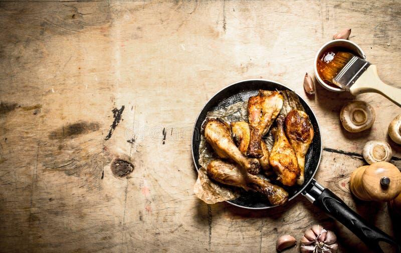在平底锅的炸鸡腿用西红柿酱 库存图片