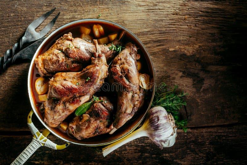 在平底锅的烤兔子腰臀部分在土气木表上 免版税库存图片