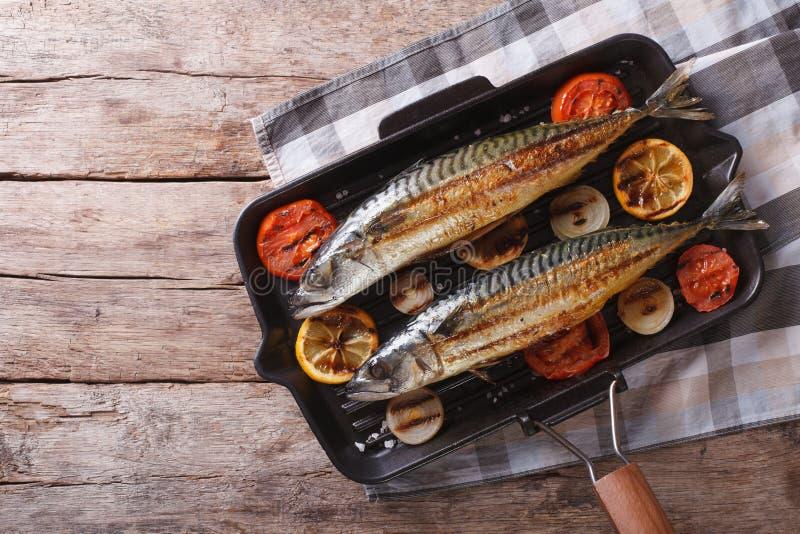 在平底锅的烤鲭鱼有菜的 水平的顶视图 图库摄影