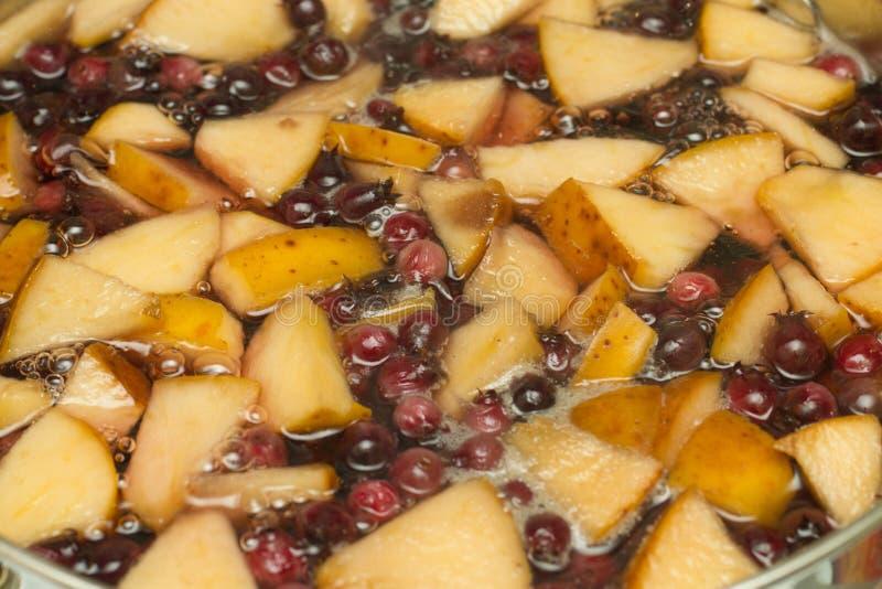 在平底锅的煮沸的苹果6月莓果蜜饯 免版税库存照片