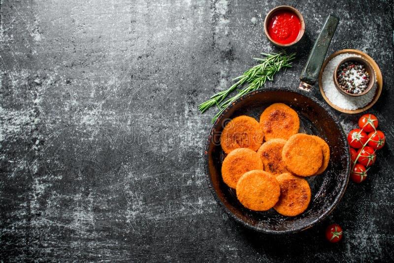 在平底锅的鱼炸肉排用香料、调味汁、迷迭香和蕃茄 库存照片
