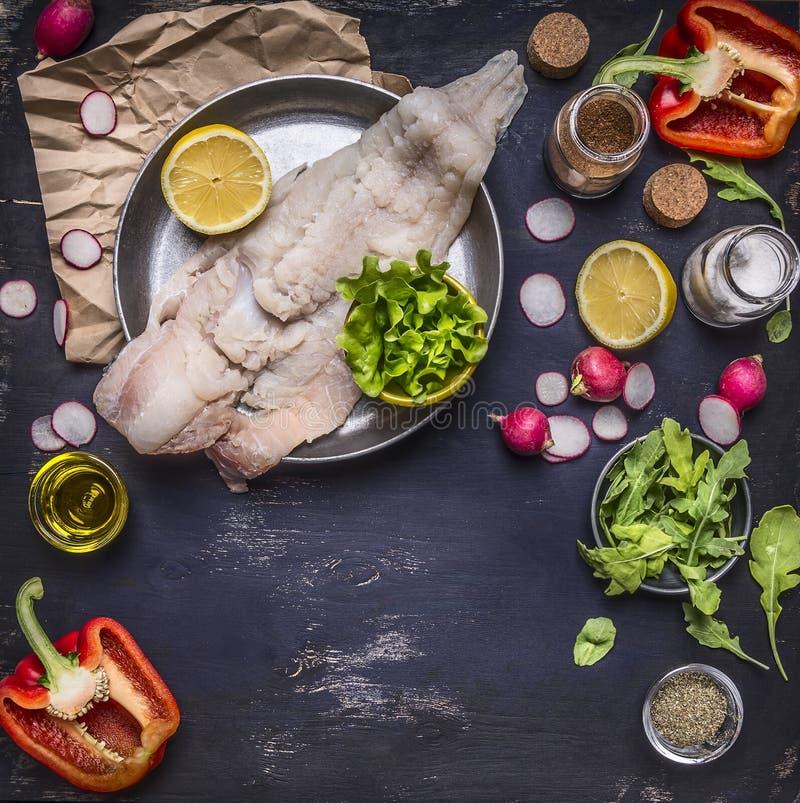 在平底锅萝卜用黄油和季节的未加工的鳕鱼有胡椒和草本柠檬深蓝土气木背景顶视图 库存图片