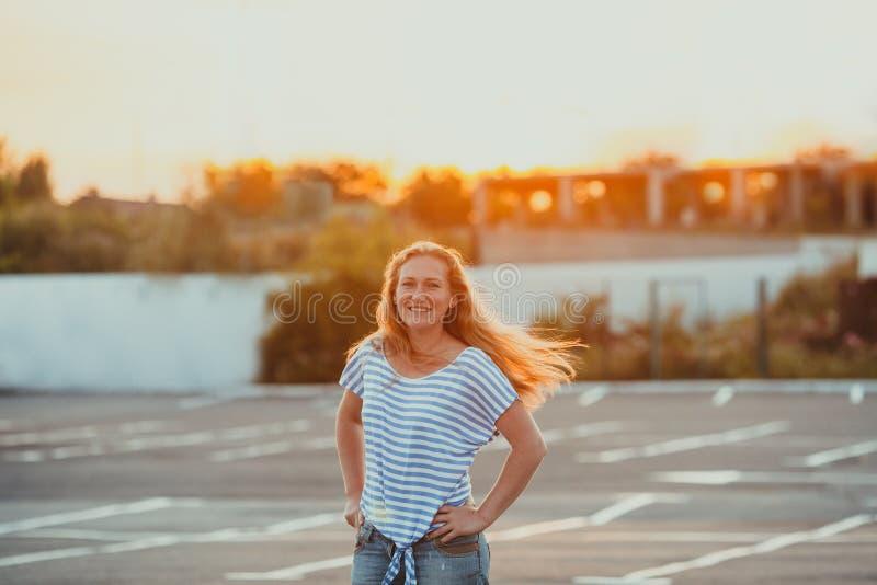在平衡太阳光芒的微笑的妇女身分  免版税库存照片