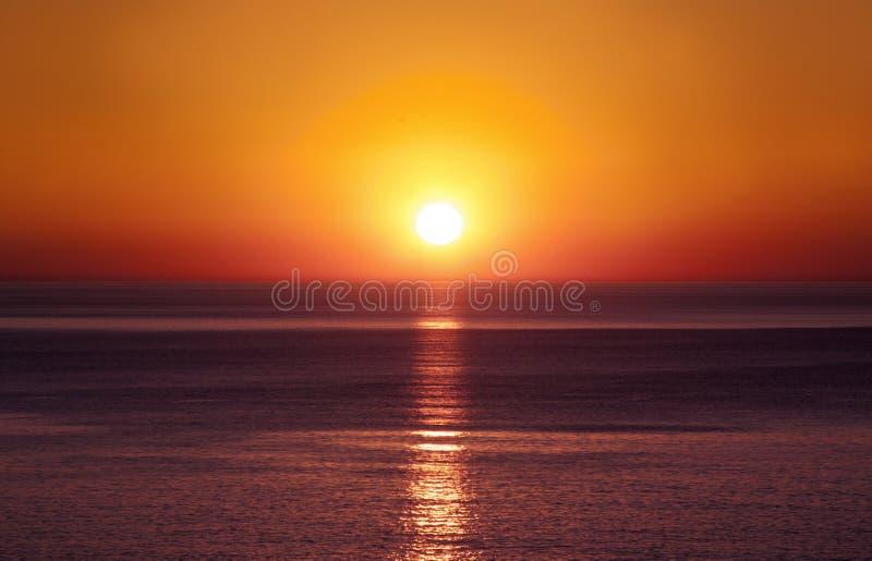 在平静的夜晚,海上的日落 免版税库存图片