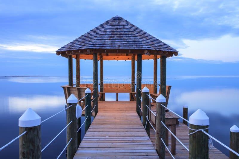 在平静的大海的眺望台在微明 免版税库存图片