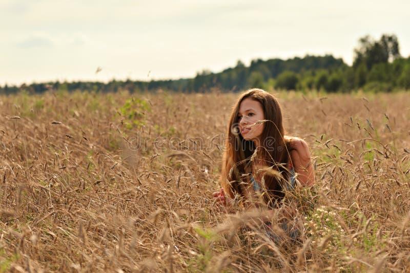 在平静的晚上日落的光芒在一块麦田的在小尖峰后是一件减速火箭的礼服的一个女孩 免版税图库摄影