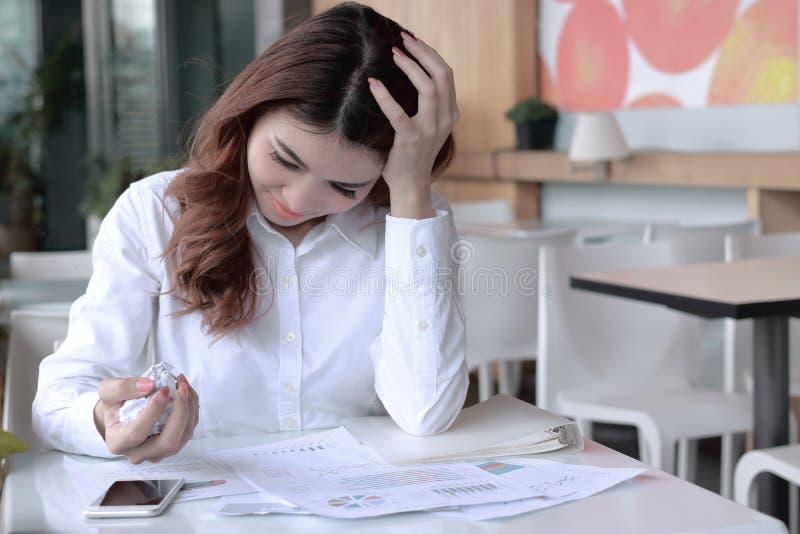 在年轻亚洲雇员藏品被弄皱的纸和感觉重音的手上的选择聚焦反对她的工作在办公室 免版税库存图片