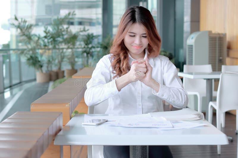 在年轻亚洲雇员藏品被弄皱的纸和感觉重音的手上的选择聚焦反对她的工作在办公室 库存照片