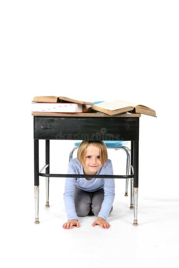 在年轻人之下的服务台女孩隐藏的学&# 免版税库存图片