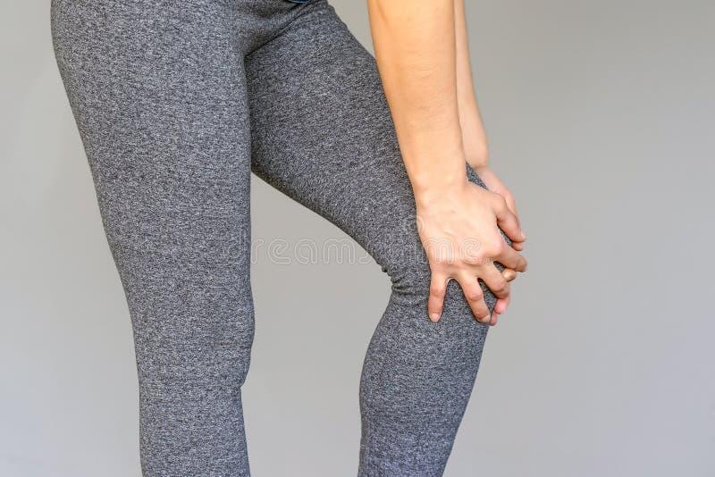 在年轻女人的膝盖的痛苦 库存图片