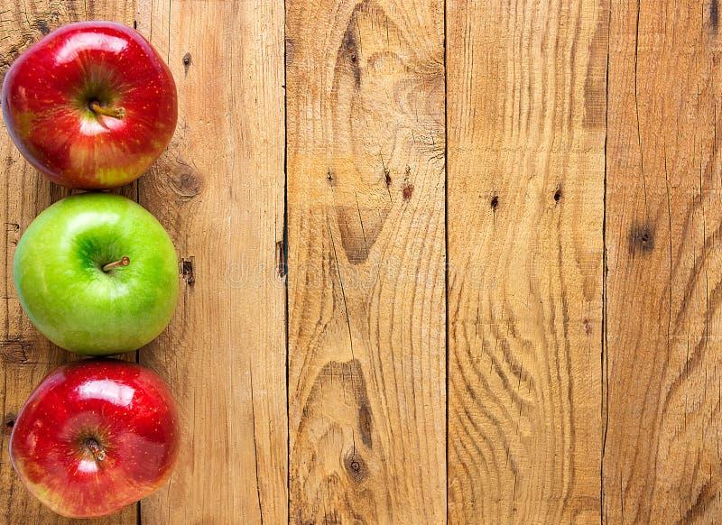 在年迈的板条谷仓木头背景的美丽的光滑的红色绿色苹果 秋天秋天收获感恩概念 土气葡萄酒 免版税库存照片