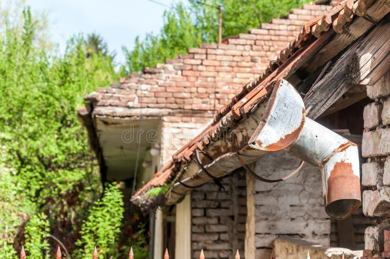 在年龄和水接近之前损坏的被放弃的房子的老和生锈的雨天沟 免版税库存图片