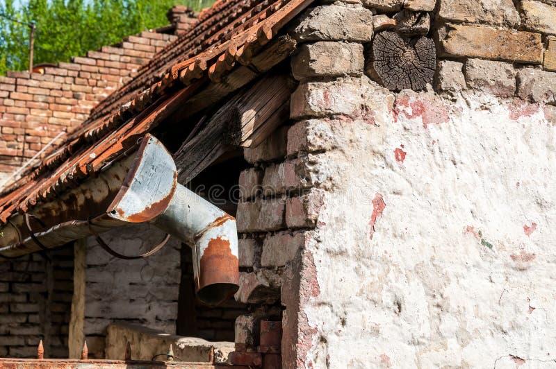 在年龄和水接近之前损坏的被放弃的房子的老和生锈的雨天沟 库存照片