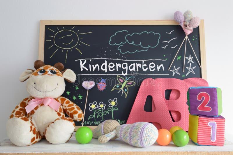 在幼儿园教室和一些婴孩材料的黑板 图库摄影
