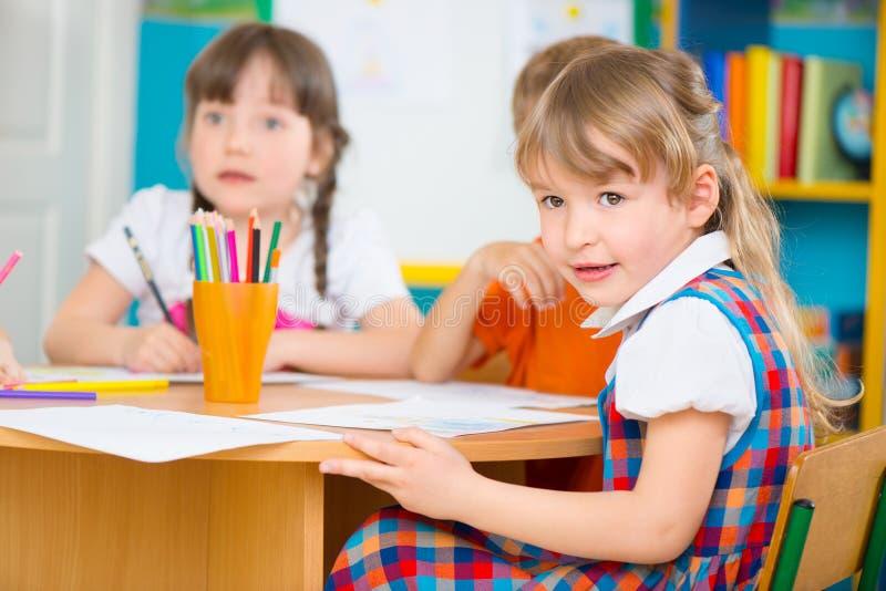 画在幼儿园的两个小女孩 免版税库存照片