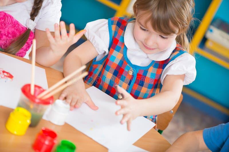 绘在幼儿园的逗人喜爱的孩子 库存图片