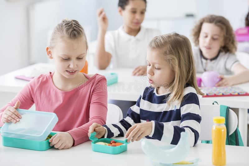 在幼儿园类的快餐时间 打开他们的薄菏的孩子 免版税库存照片