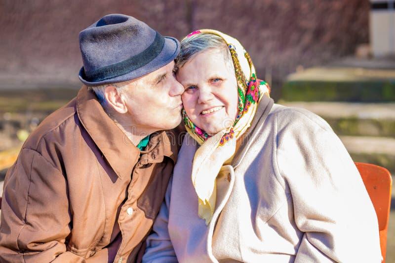 在庆祝他们的周年的爱的愉快的年长夫妇 一个愉快和爱恋的年长人亲吻他面颊的心爱的妻子 库存图片