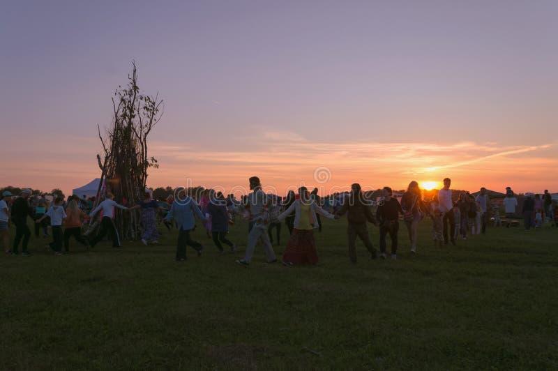 在庆祝夏至的篝火附近的圆圈舞在日落 图库摄影