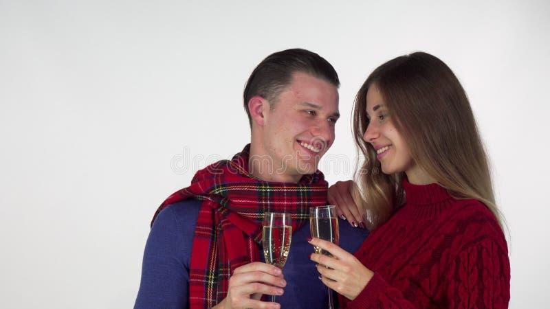 在庆祝某事,使叮当响的香槟玻璃的冬天衣物的愉快的夫妇 免版税库存照片