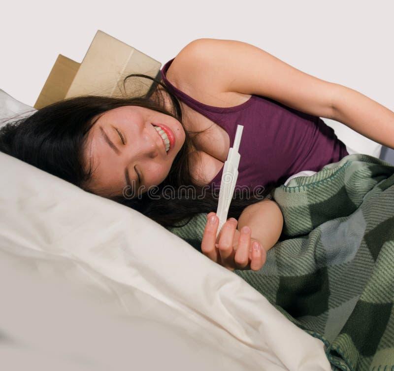 在床上举行妊娠试验检查惊奇的正面怀孕的结果微笑的ecsta的年轻愉快和激动的亚裔韩国妇女 库存照片