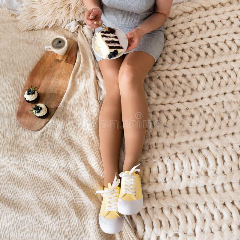 在床上吃早餐手的年轻女人拿着在腿的蛋糕 咖啡和杯形蛋糕在盘子 r r 库存图片