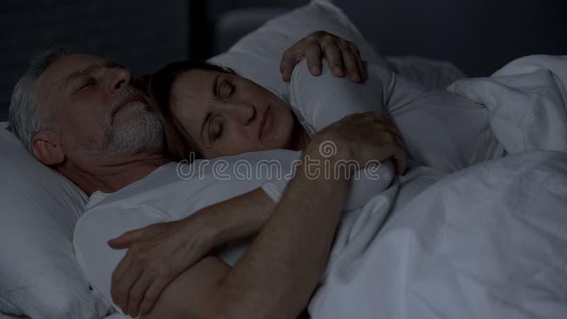 在床上和拥抱夫人的资深夫妇说谎在男性胸腔,强的婚姻 免版税库存图片