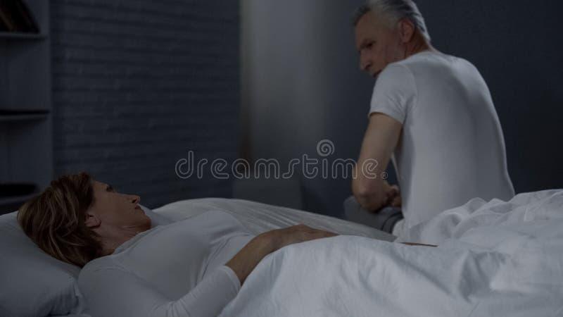 在床上和看丈夫的夫人坐床远的边缘,冲突 库存图片