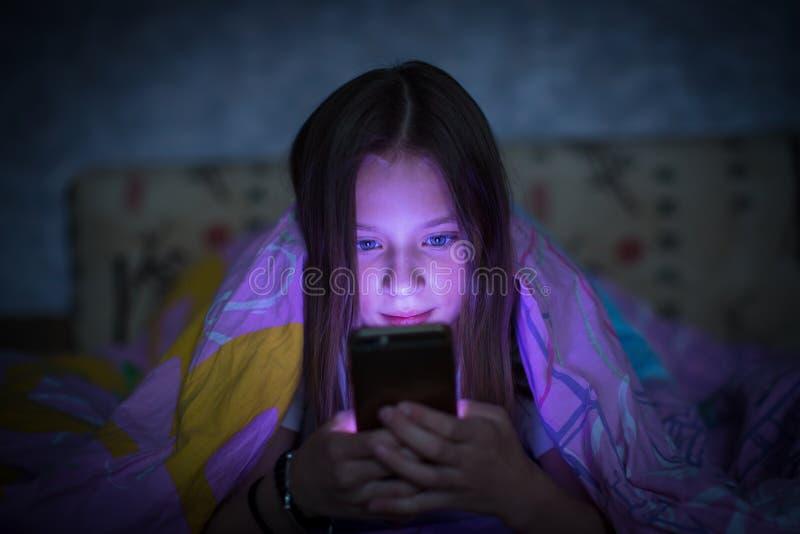 在床上和看智能手机的发光的屏幕青少年的女孩 免版税库存照片