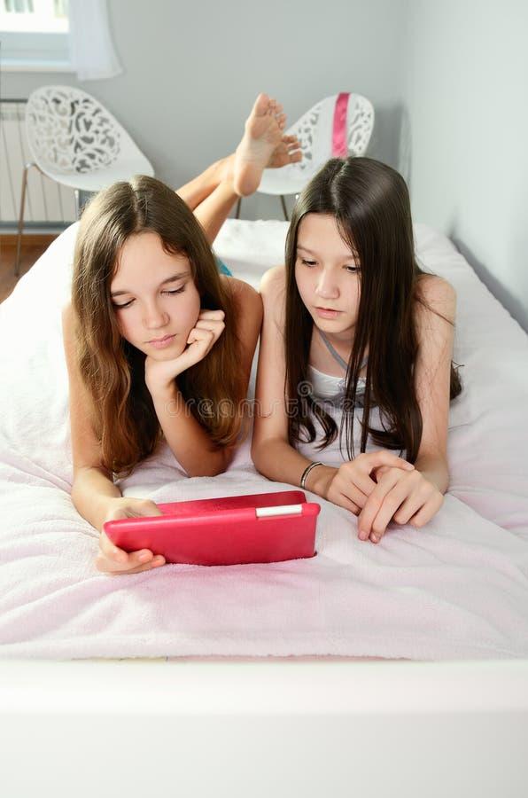 在床上和看片剂的两个女孩 垂直 免版税库存图片